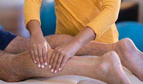 A Woman Giving a Man a Leg Massage at Home