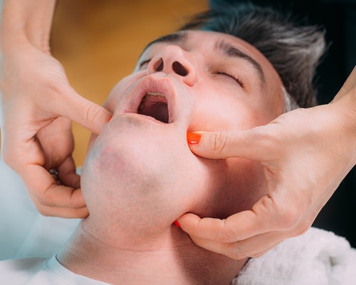 Client treating TMJ with a TMJ massage